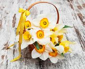 stock photo of daffodils  - Basket with daffodil flowers on a old wooden bacground - JPG