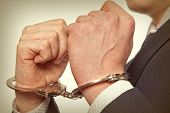 image of handcuffed  - Arrested business man handcuffed hands - JPG