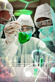 image of beaker  - Science and medical graphic against chemists in protective suits looking at green liquid in beaker Chemists in protective suits looking at green liquid in beaker in the lab - JPG