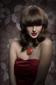 stock photo of big lips  - Pretty mysterious gorgeous woman with smooth brown hair with straight fringe wearing red satin top big old necklace and red lipstick her eyes are in shadow - JPG