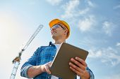 business, building, industry, technology and people concept - smiling builder in hardhat with tablet poster