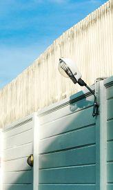 stock photo of lamp post  - street lamp at post at wall with sky - JPG