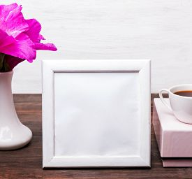 pic of text-box  - White empty frame with place for text on the table with pink flowers in a vase pink box and a cup of cofee - JPG