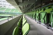 Many rows of green plastic folding seats in a big empty stadium Aviva