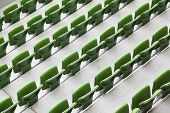 Many rows of green plastic folding seats in a big empty stadium