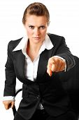 stressful modern business woman sitting on chair and pointing finger at you