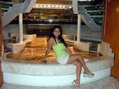 image of cruise ship  - a female sitting by a water feature in the cruise ship lobby - JPG