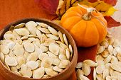 Close Up Of Healthy Pumpkin Seeds And Pumpkin Against Colorful Autumn Accents