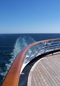 image of cruise ship  - a cruise ship at sea with the deck_rail_sky_and wake in view - JPG