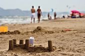 Sand castles and tourists on the beach poster