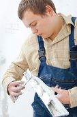 Young repairman with trowel