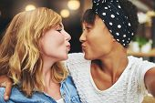 Постер, плакат: Playful Young Girl Friends Puckering Up For A Kiss