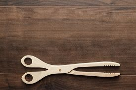foto of tong  - wooden grill tongs on the brown table - JPG