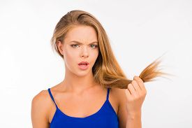 picture of split ends  - Young woman looking at split ends - JPG