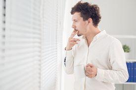 pic of jalousie  - Smoking man looking through jalousie at office - JPG