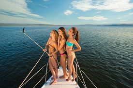 stock photo of yacht  - Girlfriends rest on a yacht in the middle of the ocean - JPG