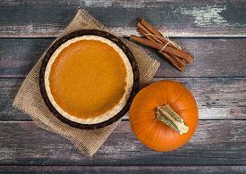 picture of pumpkin pie  - Pumpkin pie with pumpkin and cinnamon sticks against rustic wooden table - JPG