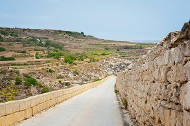 image of gozo  - Long road down from hill in sunny summer day in Gozo island Malta - JPG