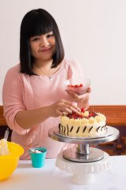 stock photo of pastry chef  - Vertical portrait of a lovely pastry chef busy with cake decorating on the foreground - JPG