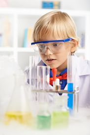 picture of chemical reaction  - Portrait of little scientist surprised with chemical reaction - JPG
