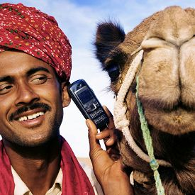 stock photo of camel  - Asian Man and Camel in the Desert with Communications Concept - JPG