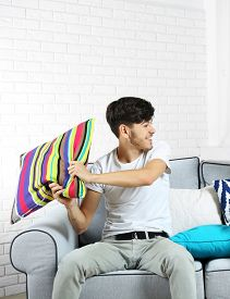 stock photo of pillow-fight  - Two brothers fighting with pillows on sofa at home - JPG