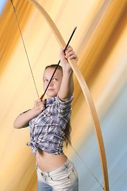 pic of archery  - Teen girl practicing archery standing on abstract background - JPG