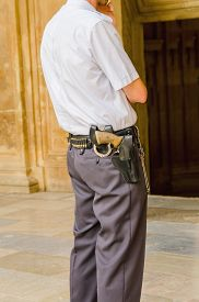 image of shackles  - Security guard standing and armed with shackles a gun and bullets - JPG