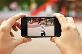 stock photo of pov  - Woman taking a photo of baby girl with smartphone  - JPG