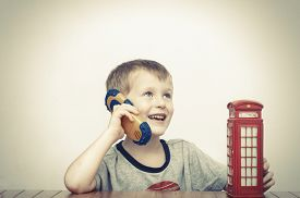 stock photo of phone-booth  - Boy talking on the phone and vintage british red telephone booth - JPG