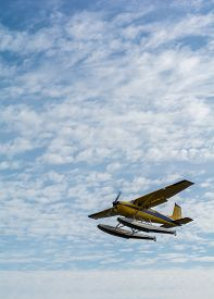 image of float-plane  - A yellow sea plane is flying over a bank of white flully clouds under a sky filled with light clouds.
