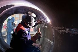 foto of welding  - The welder weld root weld from inside of the housing of chemical apparatus - JPG