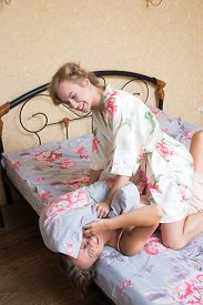 foto of pillow-fight  - Two beautiful young woman fighting with pillows in bed - JPG