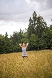 foto of stressless  - Young woman standing in an autumn field with high grass holding her hands behind her head looking up in the sky enjoying a serene moment - JPG