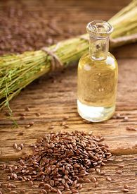 picture of flax seed oil  - Vertical photo with heap of flax seeds spilled on old worn wooden board with glass bottle full of flax oil and with bunch of flax plants bonded by natural cord - JPG