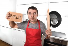 picture of panic  - funny 30s Caucasian man holding pan and rolling pin wearing red apron at home kitchen asking for help unable to cook showing panic and stress on cooking with funny face expression - JPG