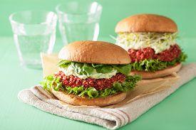 stock photo of veggie burger  - veggie beet and quinoa burger with avocado dressing - JPG