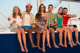 pic of yacht  - Loving couples relaxing on a yacht. Happy young people sailing on the yacht. Beautiful guys and girls spend the weekend on a yacht. Cruise on a yacht at sea. Party on a yacht. ** Note: Soft Focus at 100%, best at smaller sizes - JPG