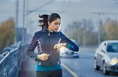 Young fitness woman runner checking time from smart watch. Young woman checking heart rate while jog poster
