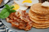Tasty breakfast with fried eggs, pancakes and bacon on plate poster