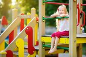 Cute Little Girl Having Fun On A Playground Outdoors In Summer. poster