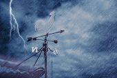 Wind Vane On House Roof With Background Of Storm Raining Windy Black Cloudy Dark Sky With Thunderbol poster