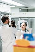 Veterinarians in Intensive Care Unit of pet clinic with cat discussing poster