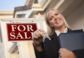 Female Real Estate Agent with Keys in Front of Sign and Beautiful House.
