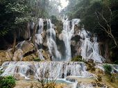Jangle Landscape With Amazing Turquoise Water Of Kuang Si Cascade Waterfall At Deep Tropical Rain Fo poster