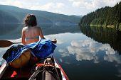 Canoeing girl on a beautiful mountain lake