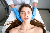 Beautician Hands In Gloves Touching Face Of Attractive Woman. Facial Beauty. Beautiful Young Female  poster