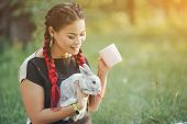Pretty Asian Girl Drinks Tea And Huggs Rabbit On Green Grass Of Summer Forest. Good-looking Girl Wit poster