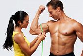 Woman measuring athletic's man biceps.