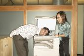Businesswoman photocopying colleague's head